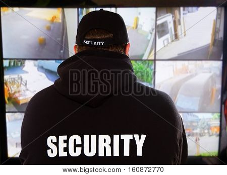 a security man looking into videosurveillance camera