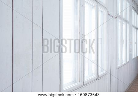 White wooden wall with windows. Old background