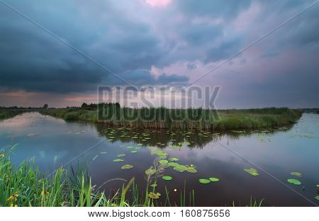wild pond during dramatic summer storm at sunset