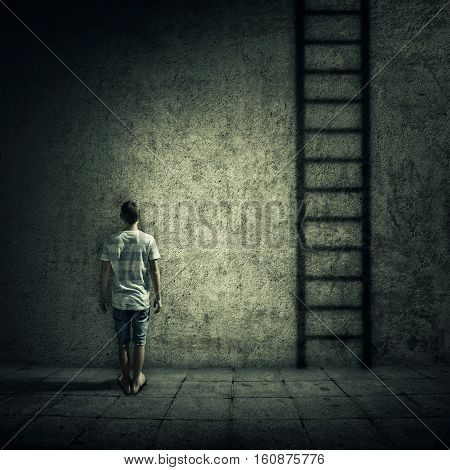 Abstract idea with a person standing in a dark room in front of a concrete wall figuring a ladder to escape. Surrounded by limitations daily routine.