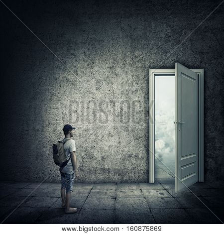 Abstract idea with a person standing in a dark room in front of a opened door. Escape opportunity entrance to another world.