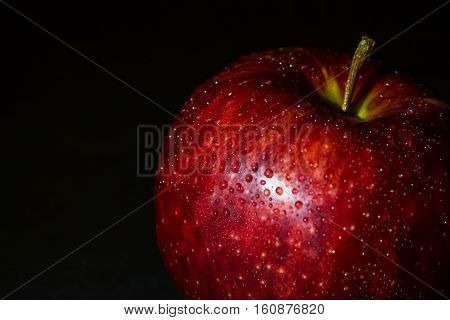 wet red apple closeup in drops of water on a black background. darkened photo