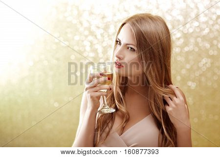 Fashion portrait of sexy blond woman with glass of champagne at party, drinking champagne over glowing background. Christmas and New year holiday