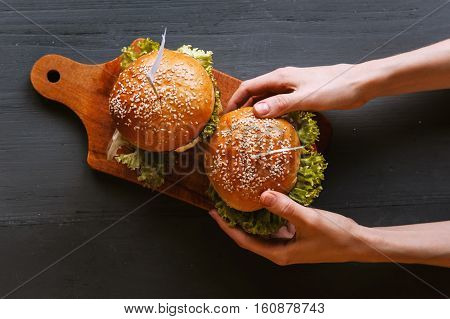 Two mouth-watering delicious homemade burger used to chop beef. on the wooden table.. girl takes a burger from the tray