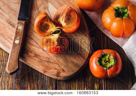 Persimmon Slices on Cutting Board with Kitchen Knife and Persimmons.
