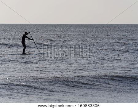 Paddleboarder braving the winter sea in January at Camber Sands near Rye in East Sussex England.