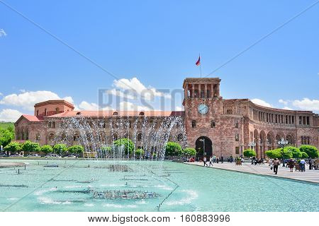 YEREVAN ARMENIA - MAY 2016: The fountain on a central square of the city of Yerevan in Armenia. State House and the national flag of Armenia.