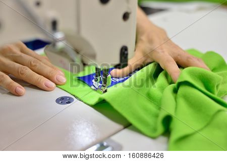 Hands seamstress at work. Logo Sew the garment. Garment factory and production.