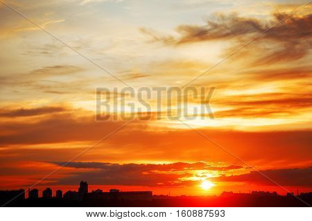 Sunrise in city landscape. Urban sunset. Rays of the sun above the town. Air photography. Dawn of a new day