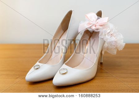 White bride's shoes garter and wedding rings. selective focus