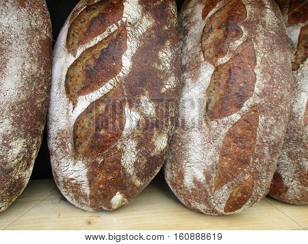 Three loaves of rustic bread sitting on a wooden shelf.