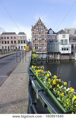 Gorinchem, Netherlands, 22 november 2016: flowers on bridge over river linge and old houses in centre of old dutch town gorinchem