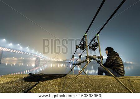 Night Fishing Urban Edition. Fisherman In Foggy Night.