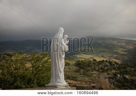 A back view of Saint Mary holding Baby Jesus overlooking a gloomy setting.