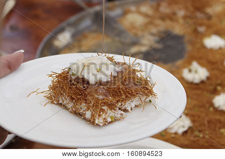 A slice piece of Esmalliyeh, a traditional Arabic sweet pastry, in a white platter with Syrop drizzling on.