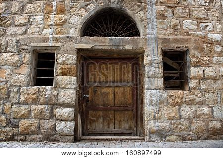 An old wooden door, windows, and wall in Lebanon.