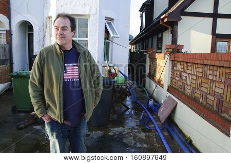 CHERTSEY, SURREY, UK - Feb 20, 2014: Mr Simon Smith outside his home in Chertsey Surrey England UK. He is still pumping out water after being flooded by groundwater after extensive flooding affected thousands of homes in the Thames Valley.