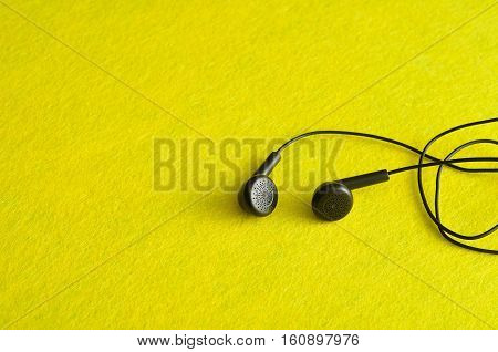 A set of earphones isolated against a yellow background