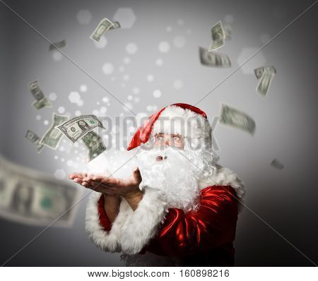 Santa Claus is blowing dollars. With best wishes for the New Year. Ironic picture. Miracle concept.