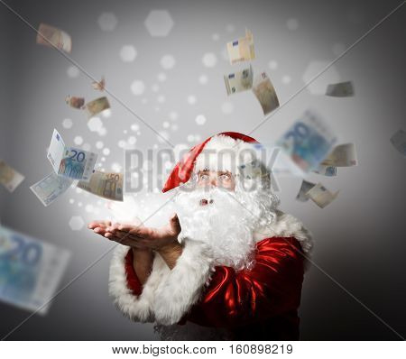 Santa Claus is blowing Euro. With best wishes for the New Year. Ironic picture. Miracle concept.