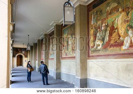 Munich, Germany - October 16, 2011: Tourists visiting the gallery in Hofgarten. Between the columns are colorful mural Peter von Cornelius, which tell about the history of the House of Wittelsbach.