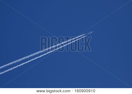 Passenger aircraft with contrails on clear blue sky