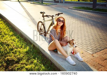 Smiling Hipster Girl with her Dog and Bike Relaxing in Park. Happy Woman Enjoying Summer Lifestyle with Pet. Candid Toned Photo with Copy Space.