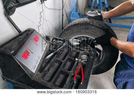 wheel balancing. Mechanic removes car tire closeup. Machine for removing rubber from the wheel disc