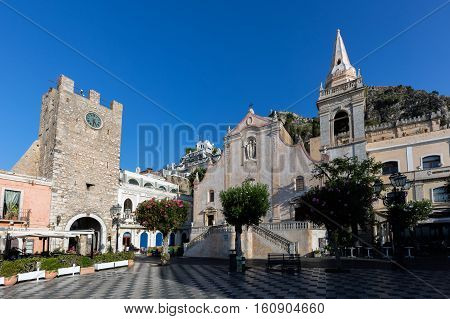 TAORMINA ITALY - AUGUST 20 2016: Church of San Giuseppe and the Taormina's Clock tower on the Piazza IX April square. The square is one of the major tourist attractions in the area.
