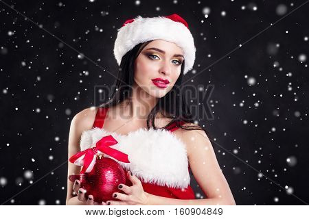 Smiling girl holding a red  Christmas tree balls. Women on dress and santa's hat. Santa's helper .Attractive happy girl in santa hat with red lips posing for camera over Christmas party black background.