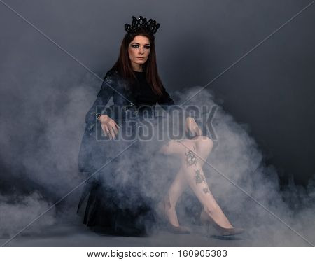Bug queen woman with crown wearing black dress with dress with luminous beetles sitting  in smoke
