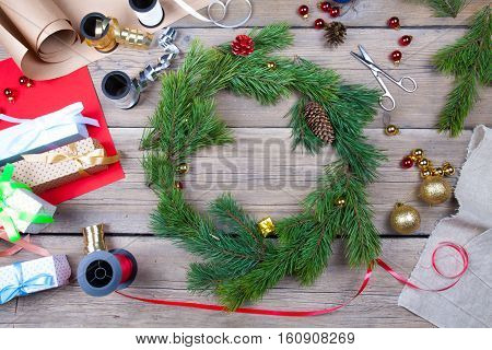 Christmas wreath on a wooden table in a workroom. Top view