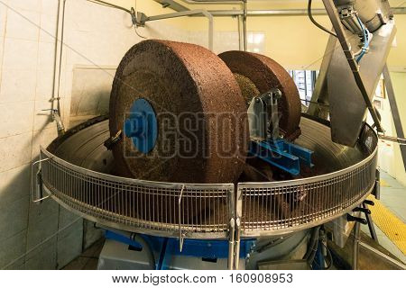 Extraction of oil from olives by means of a circular grinding stone.