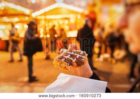 Woman Eating Christmas Traditional Waffles At Christmas Market