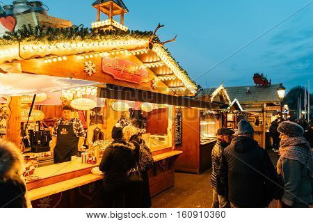 STRASBOURG FRANCE - 9 DEC 2016: Customers drinking hot wine at the traditional market stall while visiting the oldest Christmas Market worldwide in central Strasbourg Alsace