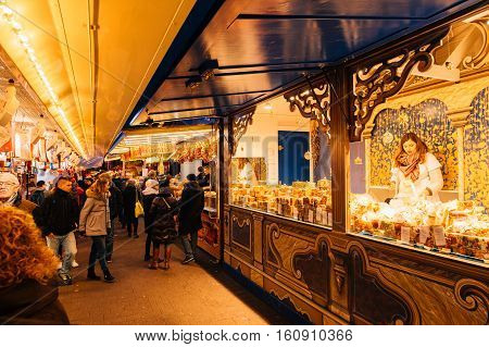 STRASBOURG FRANCE - 9 DEC 2016: People visiting the oldest Christmas Market worldwide in central Strasbourg Alsace with customers buying traditional foods and sweets from market stalls
