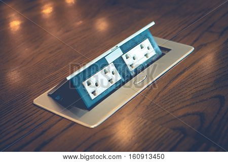 de focus of blur electric plug built in desk.