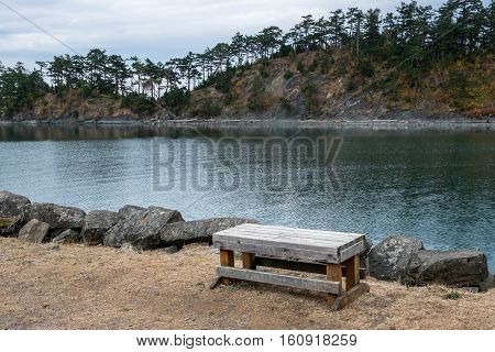Wood bench overlooking inlet on a cloudy day