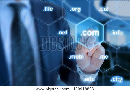 Businessman in blue touching the domain ending com on a hexagon grid in front of office background