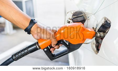 Closeup hand pumping Fuel nozzle gasoline fuel in white car at gas station