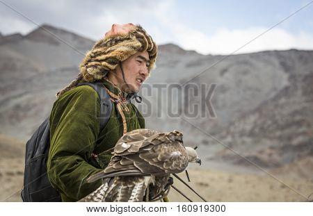 BAYAN ULGII MONGOLIA - CIRCA OCTOBER 2015: Kazakh Eagle hunter in the mountains with his eagle