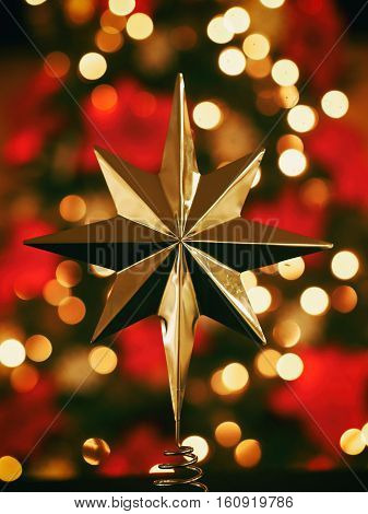gold star Christmas holiday tree topper against background of lights