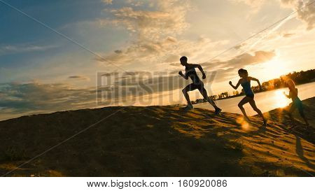 A group of athletes - two girls and a guy are fleeing the mountain, near river at dusk, silhouette