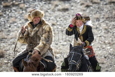 Bayan Ulgii Mongolia October 4th 2015: Eagle huntress with her dad riding a horse