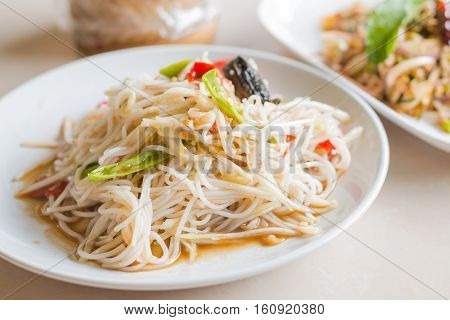 Close up Papaya Salad with Vermicelli Salted Crab and Fermented Fish Tum Sua Thai traditional food.