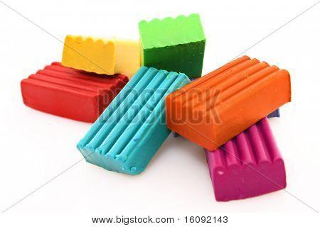 Children bright multicoloured plasticine set chaotically isolated on white