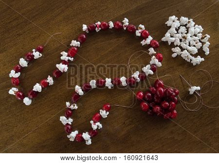 A piece of popcorn on a needle and thread being added to the popcorn and fresh cranberry Christmas garland. More popcorn and cranberries are on the wooden tabletop. Photographed from above.