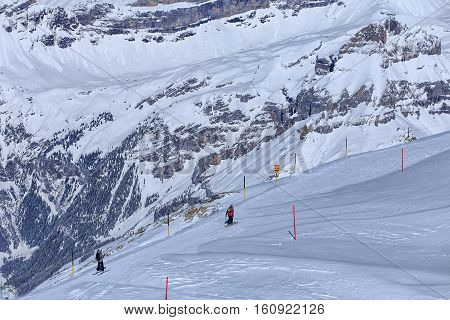 Mt. Titlis, Switzerland - 9 March, 2016: view from the mountain with people skiing. Titlis is a mountain located on the border between Swiss Cantons of Obwalden and Bern, mainly accessed from the town of Engelberg.