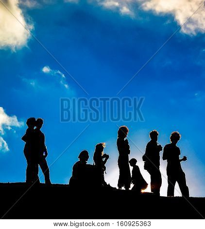 Silhouetted People On A Mountain
