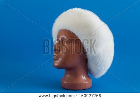 White beret from natural mink on a mannequin